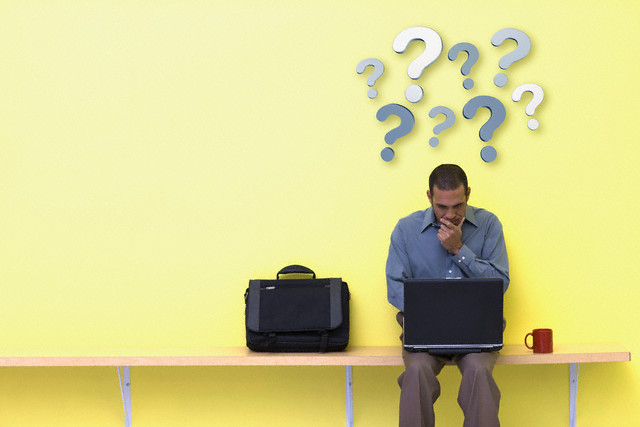 Businessman with Question Marks Over Head